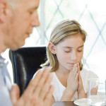 Family Folding Hands and Praying at Table
