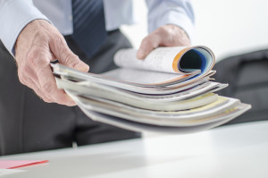 Businessman holding magazines at office