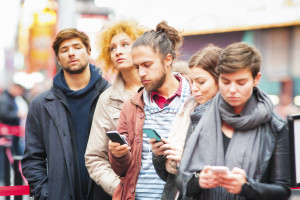 Five young adults waiting in line in Manhattan, some are using phones to pass the time while the two without phones look exasperated.