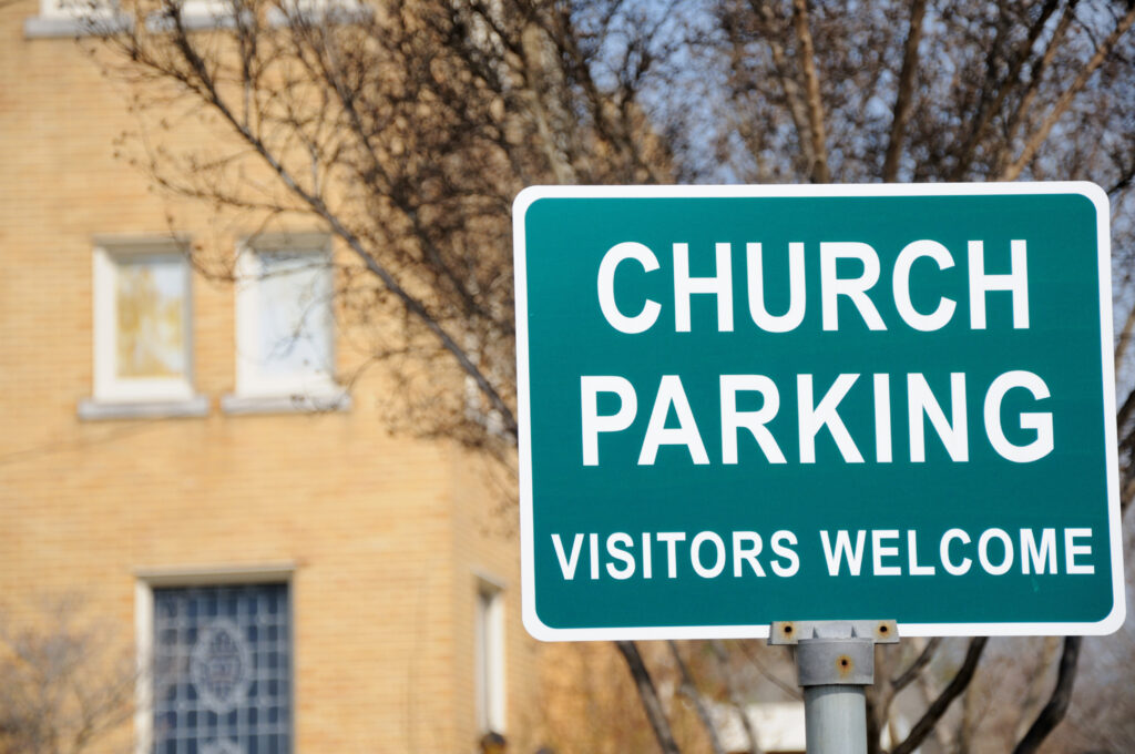 """Close up of church parking visitors welcome sign, horizontal."""