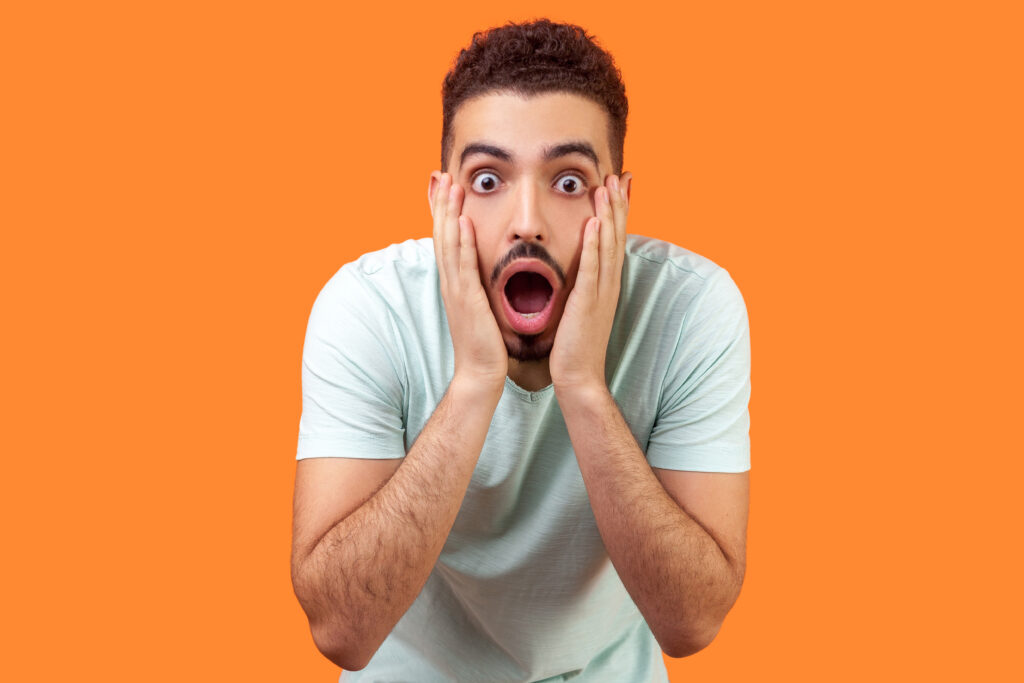 Unbelievable shocking news! Portrait of stunned brunette man with beard in casual white t-shirt holding face and keeping mouth wide open in amazement. indoor studio shot isolated on orange background